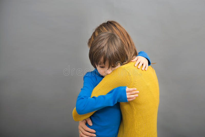 Sad little child, boy, hugging his mother at home, isolated image. Copy space. Family concept stock photo
