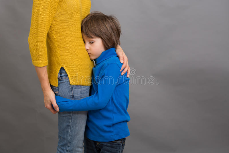Sad little child, boy, hugging his mother at home, isolated image. Copy space. Family concept royalty free stock photography