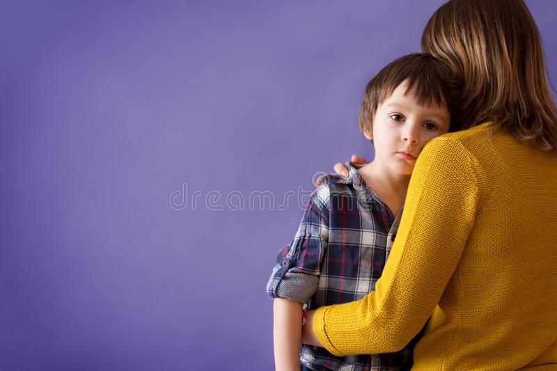 Sad little child, boy, hugging his mother at home. Isolated image, copy space. Family concept stock photography
