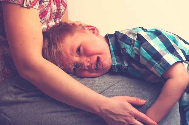 Sad little crying boy hugging his mother at home. Woman comforting her unhappy child. Family relations problems stock photo