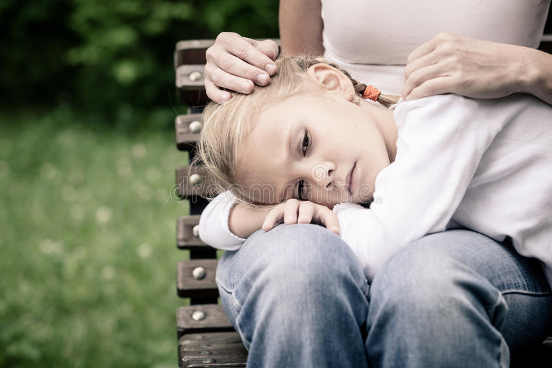 Sad mother and daughter sitting on bench in the park. At the day time royalty free stock images