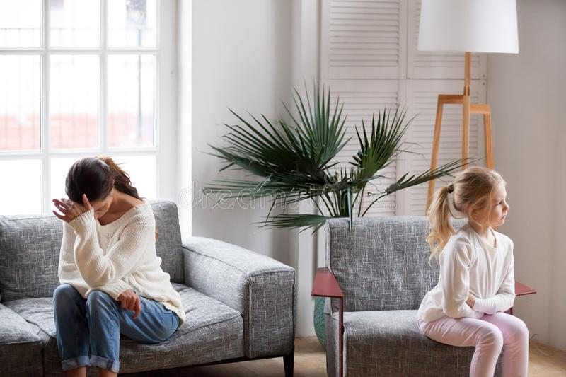 Sad tired mother and sulky daughter not talking after conflict. Sad tired mother and sulky angry offended child girl not talking after conflict in living room royalty free stock photography