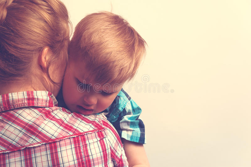 Sad unhappy child hugging his mother. Young mother comforting her little boy. Sad unhappy child hugging his mother. Family relations problems stock images