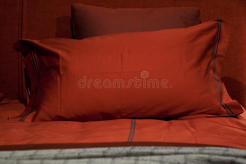 Stylish comfortable red pillows on the bed in the bedroom stock image