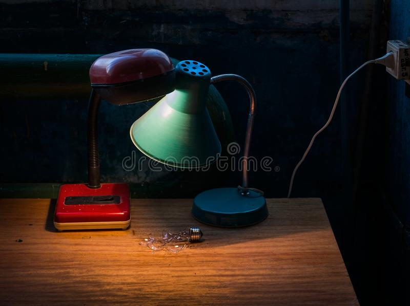 Two lamps. Still life. Two old lamps. One Broken filament lamp. Production still life royalty free stock photo