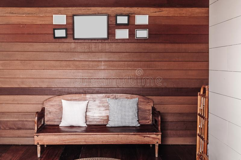 Vintage old wooden wall living room with wooden couch, pillows, stock photo