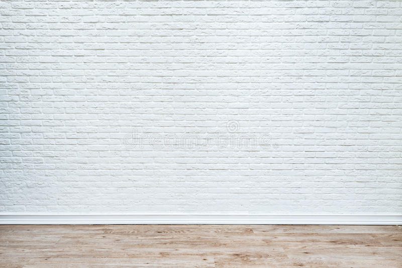 White brick wall and plank wood floor. stock photo