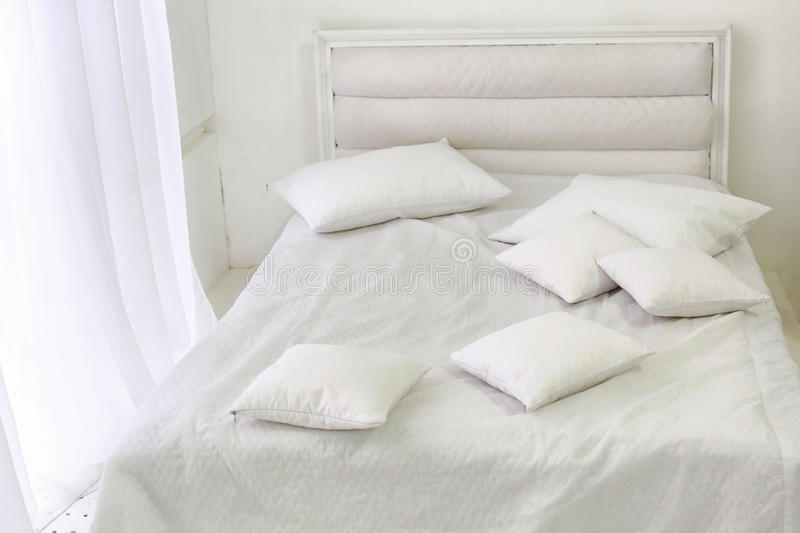 White room interior with bed, window, pillows stock photo