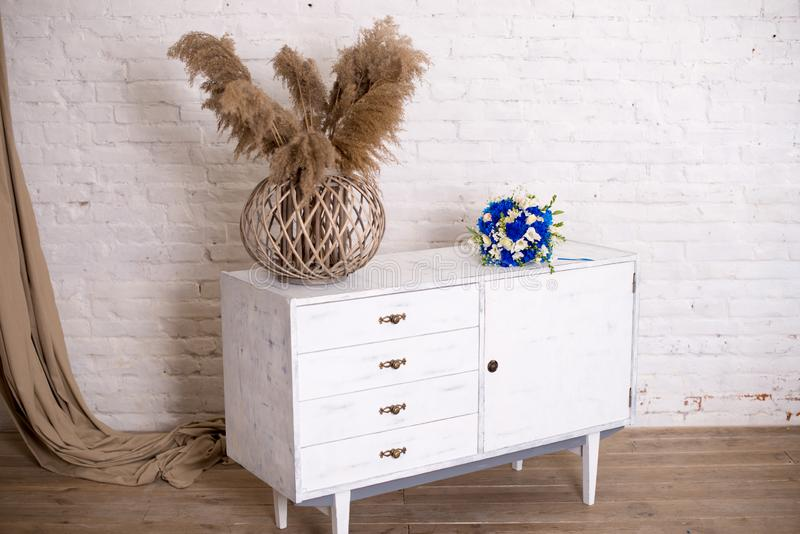 White wood bedside table, dresser in bedroom. bridal bouquet on the nightstand vase with flowers. interior. Series of stock photos
