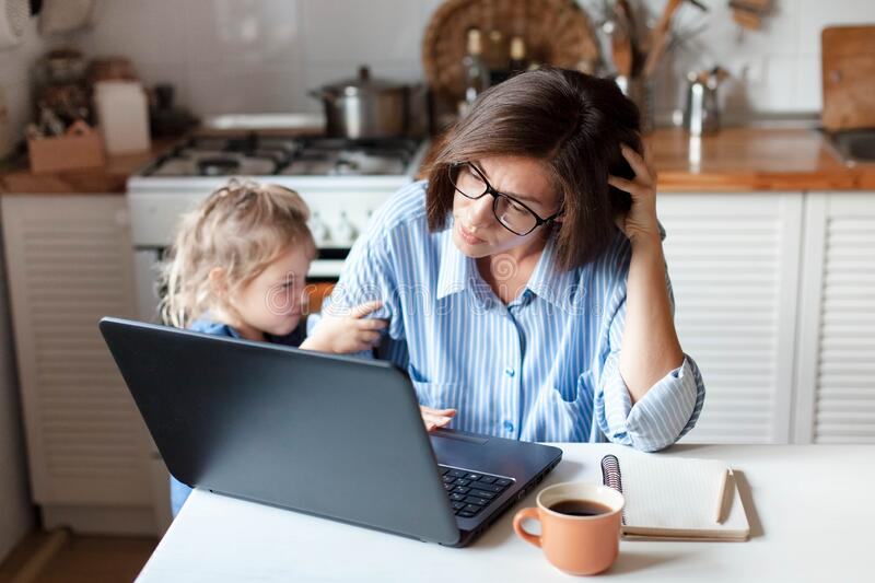 Working mother in home office. Unhappy woman and child using laptop. Sad and angry daughter. Needs attention from busy exhausted mom. Freelancer workplace in royalty free stock photography