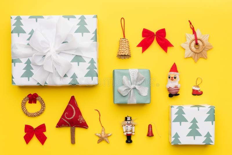 Wrapped christmas gifts and many retro christmas ornaments isolated on bright yellow background. Christmas composition. royalty free stock image