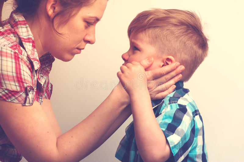 Young mother comforting her little crying child. Young mother comforting little crying boy. Sad unhappy child looking to the mom . Family relations problems royalty free stock photos