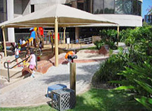 Children playing on the mulit-level play areas with sun shades overhead on a child development center playground in Hawaii